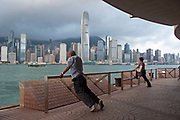Workers wait for a boat that will pick them up for their days work in Kowloon, Hong Kong, China. While waiting, young and old do morning stretches. At approximately 6am workers start to gather here near the Star Ferry terminal. The Hong Kong skyline, dominated by the Bank of China building towers over Hong Kong Harbour in the morning light.
