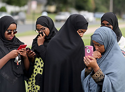 August 5, 2017 - Bloominton, Minnesota, U.S. - Wearing traditional hajibs and holding cellphones, female members of the Dar Al Farooq Islamic Center observe as Center officials speak to media after an early morning explosion at the Dar Al Farooq Islamic Center in Bloomington. No injuries were reported. (Credit Image: © David Joles/TNS via ZUMA Wire)