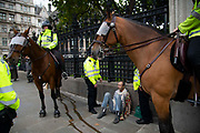 A man is detained by police officers outside the Houses of Parliament  on 7th October, 2019 in London, Untited Kingdom. Extinction Rebellion plan to occupy 12 sites situated around key Government locations around Westminster for two weeks to protest against climate change. (photo by Claire Doherty/In Pictures via Getty Images)