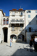 """Street scene with medieval buildings with balcony and """"na koljeno"""" style of door/window/counter--traditionally the door was closed and the horizontal surface became the counter over which trade was conducted. Diocletian Palace, Split, Croatia"""