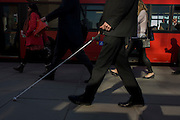 Unsighted or partially-sighted pedestrian crosses London Bridge during the evening rush hour.