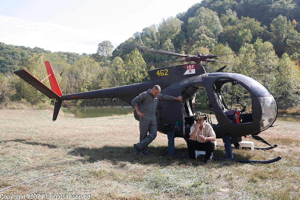 """Jim """"Blackie"""" Black, who served with the 1st Squadron, 9th Cavalry in 1967 and 1968 during the Vietnam War, right, helps with Red Horse Aviation's OH-6 Loach during the Machine Gun Shoot at Knob Creek, Kentucky, October 12, 2007. The Vietnam era OH-6 Cayuse, was commonly called a Loach during the Vietnam War. ."""