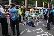Metropolitan Police officers ask activists from HS2 Rebellion, an umbrella campaign group comprising longstanding campaigners against the HS2 high-speed rail link as well as Extinction Rebellion activists, to leave the road outside the Department for Transport during a protest on 4 September 2020 in London, United Kingdom. Activists glued themselves to the doors and pavement outside the building and sprayed fake blood around the entrance during a protest which coincided with an announcement by HS2 Ltd that construction of the controversial £106bn high-speed rail link will now commence.