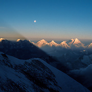 The full moon rises above the shadow of Mount Everest arcing across the spine of the Himalaya; from Camp V at 25,600 feet on the North Ridge, Tibet, China.