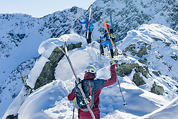 Rear view of skiers climbing on snow mountain