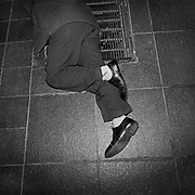 A homeless man sleeps on a grate which is the exhaust vent for heating an office tower on Bay Street located in Toronto's Financial District..(Credit Image: © Louie Palu/ZUMA Press)