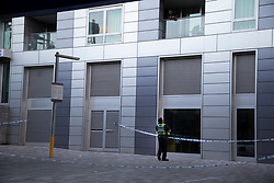 © Licensed to London News Pictures. 10/07/2020. London, UK. A Police officer speaks to a member of the public at a crime scene near Crossharbour DLR station in Poplar. Police were called shortly after 18:00hrs to reports of two males injured at Alexia Square, E14 close to Crossharbour DLR station. Officers attended and found a man, believed aged in his late teens or early 20s, suffering stab injuries. Emergency services provided first aid but despite their efforts, he was pronounced dead at the scene. A second male, believed aged in his late teens, was taken by the LAS to an east London hospital. Photo credit: George Cracknell Wright/LNP