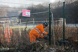 Harefield, UK. 21 January, 2020. A man wearing high-visibility clothing adjusts fencing on Harvil Road during preparation work for the HS2 high-speed rail link.