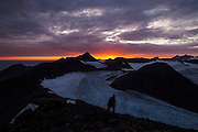 Damian Zieba hikes up Fugleberget at sunset above the Polish Polar Station in Hornsund, Svalbard. The upper tributaries of Hansbreen are visible behind him.