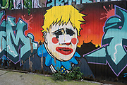 Boris Johnson clown street art mural in Spitalfields on 10th August 2021 in London, United Kingdom. The British Conservative Prime Minister has often been lampooned in this type of portrayal as Bojo the clown, as a figure of amusement in politics. Street art in the East End of London is an ever changing visual enigma, as the artworks constantly change, as councils clean some walls or new works go up in place of others. While some consider this vandalism or graffiti, these artworks are very popular among local people and visitors alike, as a sense of poignancy remains in the work, many of which have subtle or political messages.