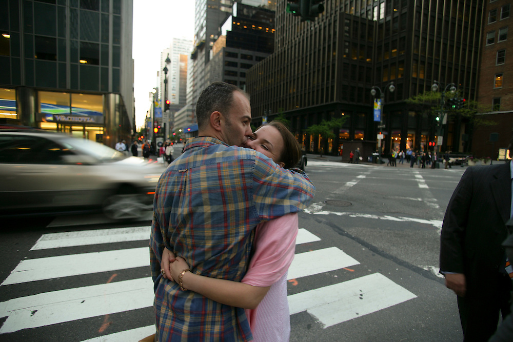 A couple kisses while waiting on a crosswalk in Manhattan, New York.