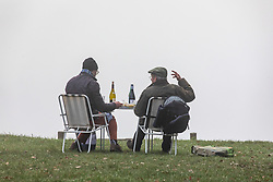 © Licensed to London News Pictures. 07/12/2020. Surrey, UK. Two walkers enjoy a cheese and wine picnic in the thick fog on top of Box Hill, Surrey as the Met Office issue a yellow weather warning for freezing fog with disruption to transport for the South East of England today with temperatures near 0c. The Government is expected to rolling out the new Pfizer/BioNTech's coronavirus vaccine tomorrow with reports it has already arrived in the UK for distribution to hospitals around the country. Photo credit: Alex Lentati/LNP