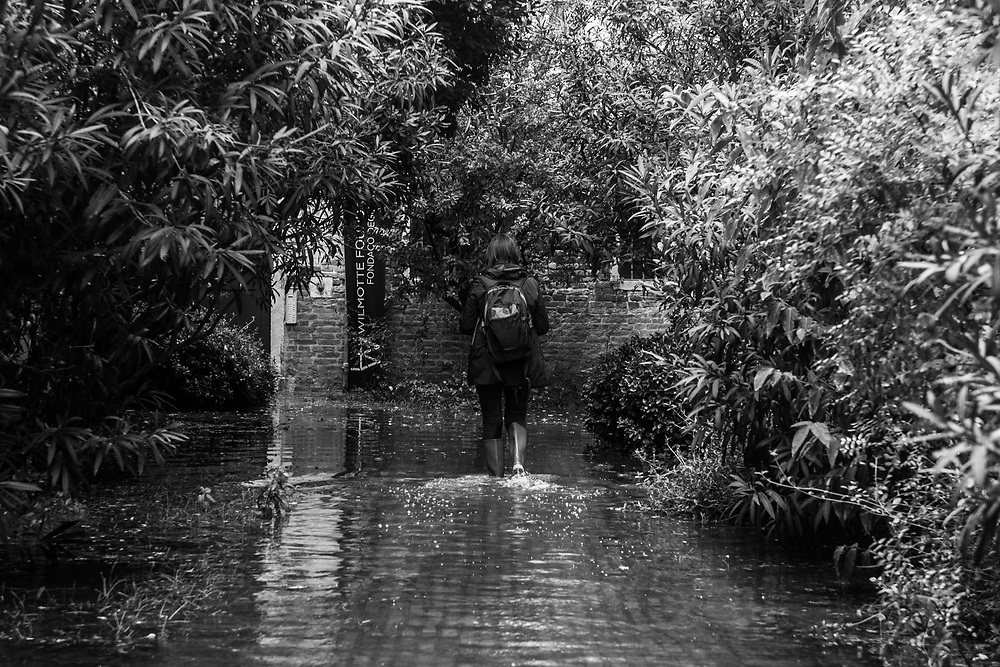 Venice, Italy. 29 October, 2018. A woman walks to reach her house through an internal garden during the high tide on October 29, 2018, in Venice, Italy. This is a selection of pictures of different areas of Venice that the press has not covered, were resident live and every year they have to struggle with the high tide. Due to the exceptional level of the 'acqua alta' or 'High Tide' that reached 156 cm today, Venetian schools and hospitals were closed by the authorities, and citizens were advised against leaving their homes. This level of High Tide has been reached in 1979. © Simone Padovani / Awakening / Alamy Live News