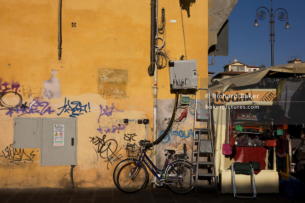 Graffiti street corner and tourist kiosk near Florence's Piazza Santa Croce. It is a bright morning and the sunshine illuminates the yellow wall that has been covered at ground level by the scrawls of graffiti by local youths - a facet of every corner of the city's medieval architecture.