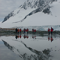 Tourists explore a cove at Damoy Point on Wiencke Island, Antarctica.
