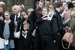 © Licensed to London News Pictures . 20/12/2017. Manchester, UK. Mourners hug and cry outside the church after the service . The funeral of 14-year-old Sam Berkley at Christ Church in Denton , East Manchester . Mourners wear red and white , the colours of Hattersley FC , for whom Berkley played . Amongst their number are pupils and friends from Audenshaw School . Berkley died after being hit by a grey BMW near junction 3 of the M67 in Hyde , East Manchester , on 1st December 2017 . Photo credit: Joel Goodman/LNP