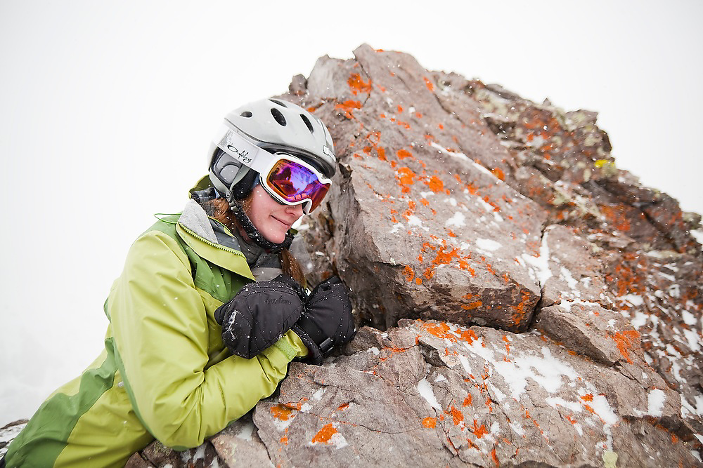 Backcountry skier Sarah Conlin leans against a boulder covered in colorful lichen in the high alpine below Hayden Peak, San Juan Mountains, Colorado.
