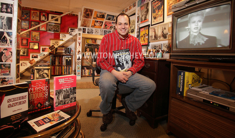 """John DiLeo of Milford, Pa., holds one of the four books he's published on movies while sitting in in his basement, which is filled with film memorabilia. A scene from """"Bachelor Mother"""" with Ginger Rogers is on the television screen.  His other three books are on the table at left."""