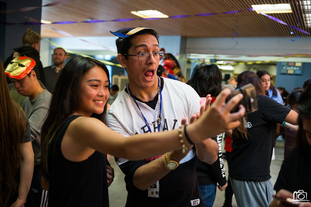 Mountain View High junior Edgar Tapia, right, and Allison Feraren take selfies during the Best Buddies Special Education Dance at Milpitas High School in Milpitas, California, on April 21, 2017. (Stan Olszewski/SOSKIphoto)