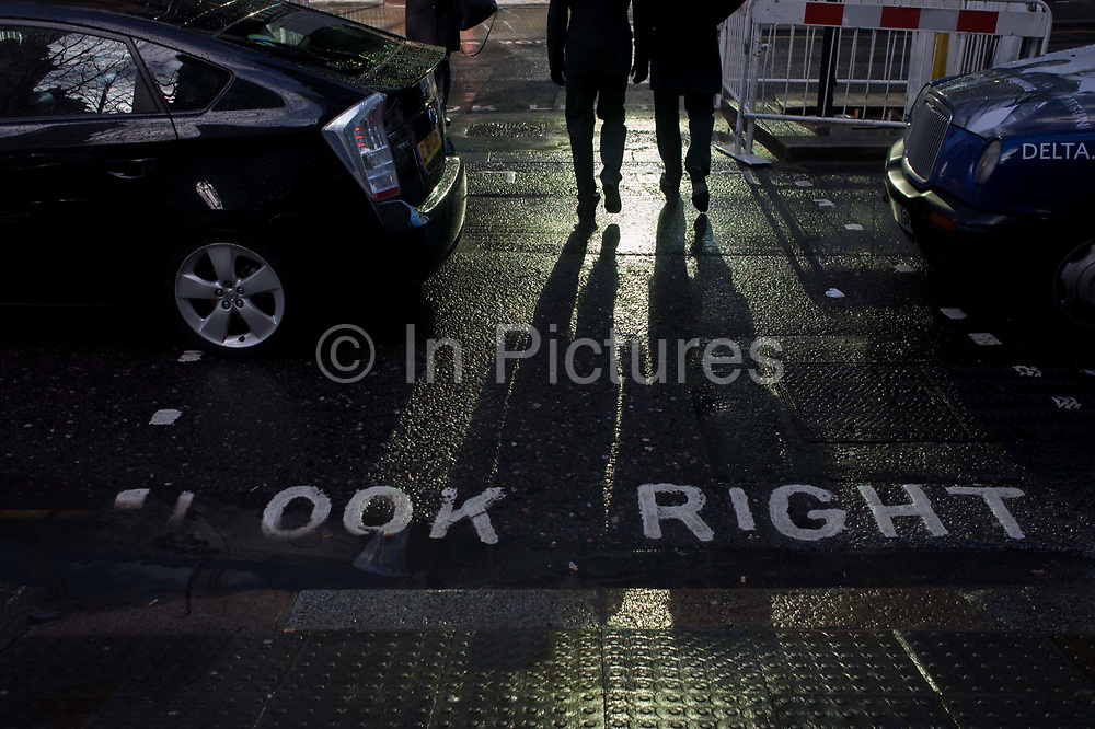 In strong sunlight, pedestrians in the financial City of London's Threadneedle Street cross the road in front of traffic still wet after recent showers. The words Look Right are seen stencilled in the road surface that glistens in recent rain and shining in light reflected from nearby plate-glass windows. Two male figures are walking away from the kerb towards the centre of a traffic island, surrounded by roadworks barriers. Their long shadows stretch across to the foreground kerb in the heart of the financial City of London, known as the Square Mile after its ancient Roman walled past.