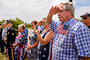 29 AUGUST 2020 - RUNNELLS, IOWA: A man salutes at the funeral for Pvt. Roy Brown Jr. in Runnells, IA. Pvt. Brown was a US Army soldier in World War II. He was an infantryman in the 126th Infantry Regiment, 32nd Infantry Division, serving in the Australian Territory of Papua (now Papua New Guinea). He went missing in action on Dec. 2, 1942. Unidentified remains were recovered on Feb. 2, 1943 and were eventually interred in the Manila American Cemetery. On May 14, 2019, Defense POW/MIA Accounting Agency using dental records, circumstantial evidence and DNA identified the remains as Pvt. Brown's. He was reinterred in the Lowman Cemetery in Runnells Saturday.     PHOTO BY JACK KURTZ