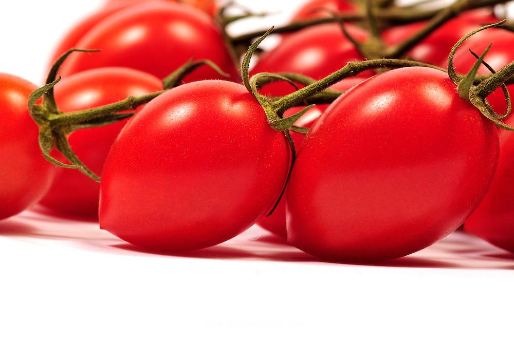 Organic vine-ripened Roma tomatoes on the vine.