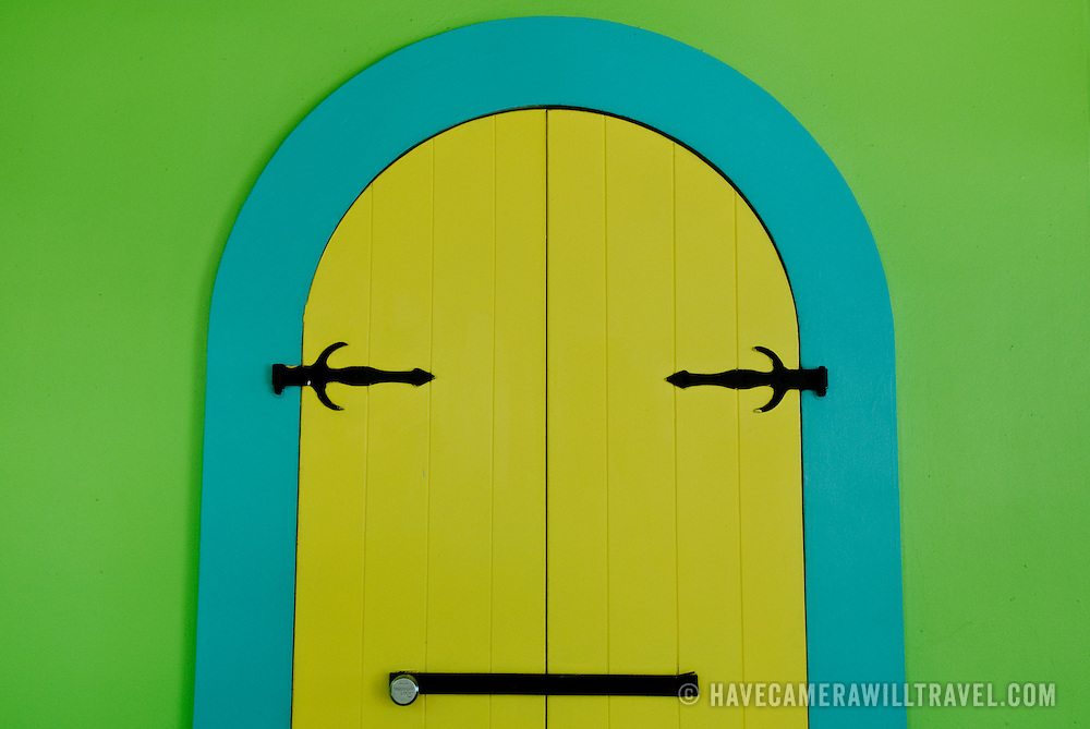 Brightly painted shuttered doorways on store in Cruz Bay
