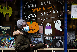 © Licensed to London News Pictures. 20/10/2020. Manchester, UK. A woman walks past a Halloween display in Manchester, reminding customers to wear a mask. Manchester is expecting to be forced in to a Tier 3 lockdown unless a deal is agreed, which could see businesses such as pubs and bars closed. Photo credit: Kerry Elsworth/LNP