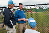 Bob Glassett and Larry Greeley of Lakes Region Home Builders chat with Austin Wilder prior to Greeley throwing out the first pitch of the game Wednesday evening at Robbie Mills Sports Complex.   (Karen Bobotas/for the Laconia Daily Sun)