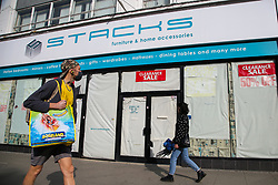 © Licensed to London News Pictures. 19/10/2020. London, UK. A man wearing a face covering in north London walks past a store which has closed due to coronavirus crisis. According to the figures, revealed by the Local Data Company and advisory firm PricewaterhouseCoopers (PwC), a total of 11,120 shops on UK high streets closed in the first half of this year due to the coronavirus lockdown.  Photo credit: Dinendra Haria/LNP