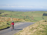 Cyclist on the steep hill up to Pym Chair from Jenkins Chapel, Peak District National Park