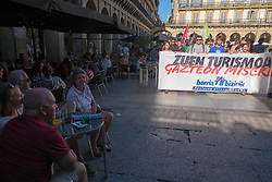"@Licensed to London News Pictures 17/08/17. San Sebastian, Basque Country, Spain. Tourists look on as protestors lead an anti-tourism march today through the crowded streets of the Basque town of San Sebastian in Spain. The banner translation from Basque is "" Your tourism is the misery of the young"". Following on from similar demonstrations in Barcelona protestors in San Sebastian are protesting against the  over-tourism of their country.  Photo credit: Manu Palomeque/LNP"