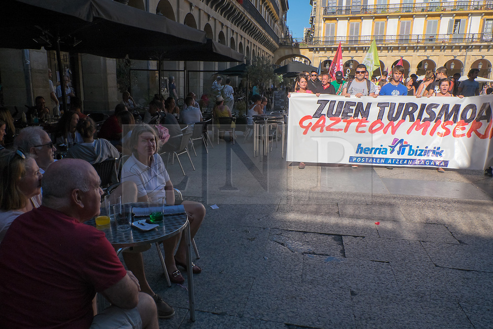 """@Licensed to London News Pictures 17/08/17. San Sebastian, Basque Country, Spain. Tourists look on as protestors lead an anti-tourism march today through the crowded streets of the Basque town of San Sebastian in Spain. The banner translation from Basque is """" Your tourism is the misery of the young"""". Following on from similar demonstrations in Barcelona protestors in San Sebastian are protesting against the  over-tourism of their country.  Photo credit: Manu Palomeque/LNP"""