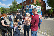 People queuing for the ice cream van in Somers Town on 1st July 2016 in London, United Kingdom. Somers Town, a district in north west London, is a large housing estate nestled between Euston, St Pancras and Kings Cross Library. Predominantly filled with social housing for the past 200 years, much of the area's housing was built in the twentieth century by the local authority.