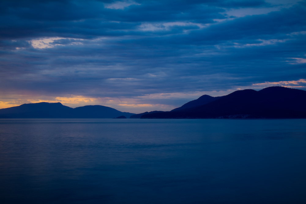 The last light fades over Rosario Strait and her scatttered islands. Photographed from an exposed cliff on Fidalgo Island, in Anacortes, Washington.