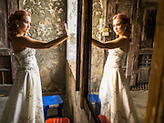 "17 MARCH 2015 - BANGKOK, THAILAND: A woman takes a ""selfie"" during a break in  prewedding photos in the old Customs House in Bangkok. With its evocative architecture and turn of the century mood, the Customs House is a popular setting for wedding photos and portraits. The old Customs House was once the financial gateway to Thailand (before 1932 called Siam). It was designed by an Italian architect in the 1880s. In the 1950s, customs moved to new, more modern building and the Customs House became the headquarters for the Marine firefighters. The firefighters now live in the decrepit buildings with their families.    PHOTO BY JACK KURTZ"