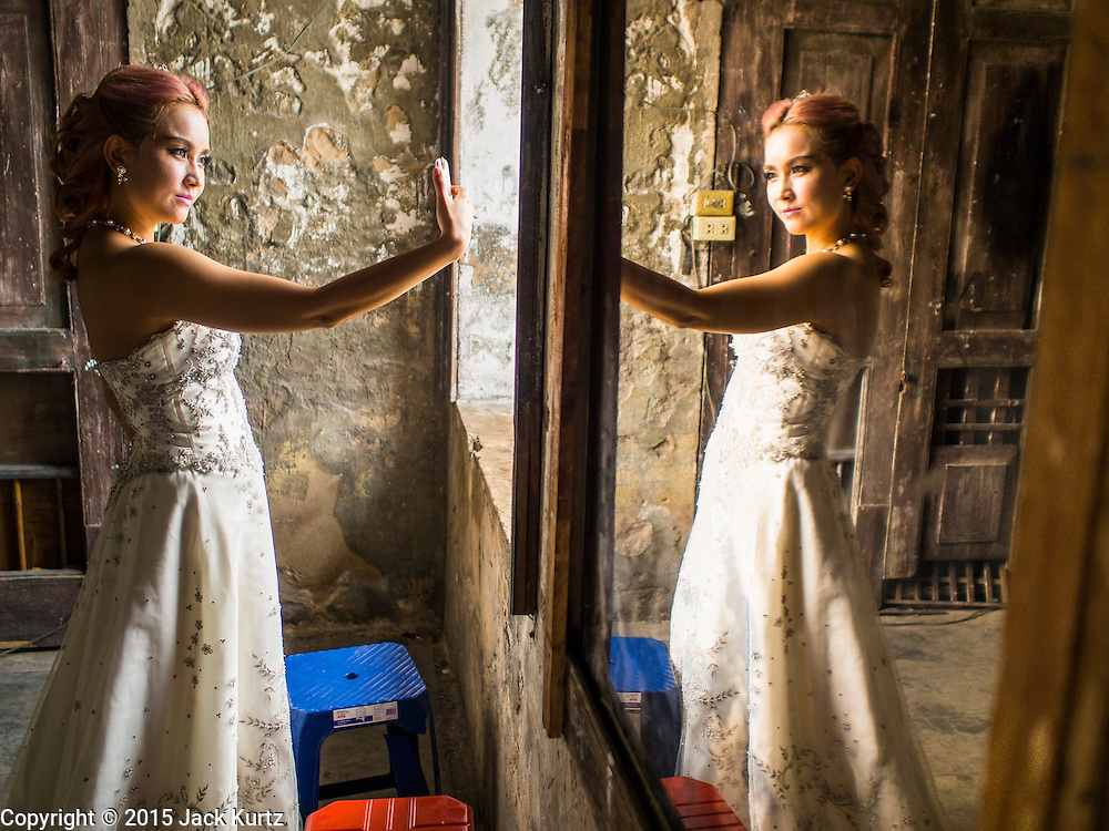 """17 MARCH 2015 - BANGKOK, THAILAND: A woman takes a """"selfie"""" during a break in  prewedding photos in the old Customs House in Bangkok. With its evocative architecture and turn of the century mood, the Customs House is a popular setting for wedding photos and portraits. The old Customs House was once the financial gateway to Thailand (before 1932 called Siam). It was designed by an Italian architect in the 1880s. In the 1950s, customs moved to new, more modern building and the Customs House became the headquarters for the Marine firefighters. The firefighters now live in the decrepit buildings with their families.    PHOTO BY JACK KURTZ"""