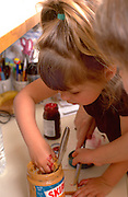 Sisters making peanut butter and  jelly sandwiches ages 3 and 5.  WesternSprings  Illinois USA