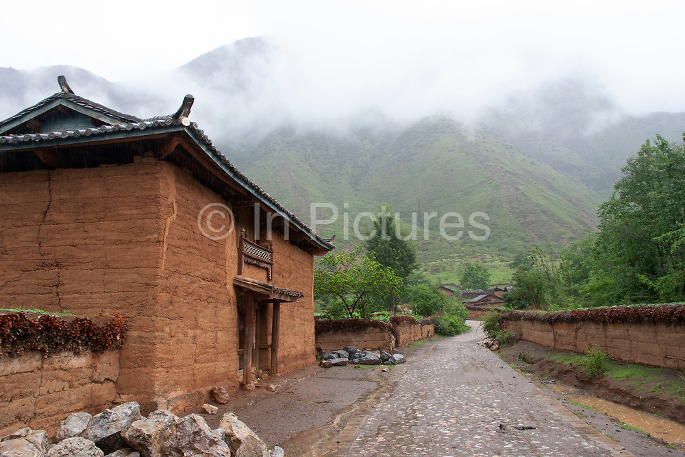 House in the shadow of Shi Zi Shan, or Lion Mountain, near the small settlement of Li Ge on Lugu Lake, Yunnan, China. Crops which have to thrive in the iron rich red soil which erodes all around due to high precipitation levels.