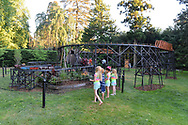 Old Westbury, New York, U.S. June 23, 2021. Children watch a Pennsylvania Railroad G gauge model train round a bend during the Old Westbury Gardens opening reception for its outdoor Great Pine Railway exhibit, which runs until September 6.