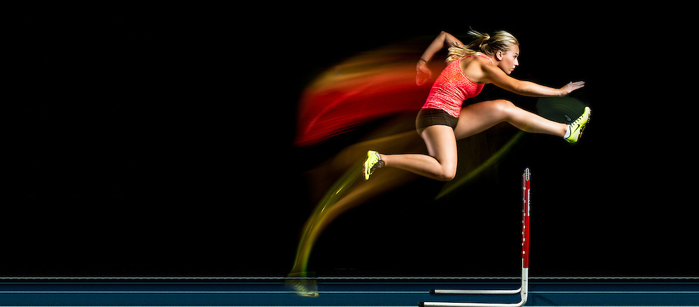 Studio capture of an athlete on the hurdles with motion blur