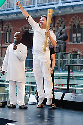 © Licensed to London News Pictures. 26/07/2012. London, UK.  London 2012 Olympics - the Olympic Torch at on its penultimate day (Day 69) of the Olympic Torch Relay at St Pancras International rail station .  Luke Corduner hands the torch over to Danny McCubbin.  Danny awaits Luke, sees him, and leaps with excitement.  Photo credit : Richard Isaac/LNP