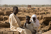Young boys watch from the rim of a large brickworks, an outdoor factory for producing building materials for more stubstantial housing in the scorched barren dirt of the 4 sq km camp Abu Shouk refugee camp which is (disputedly) home to 38,000 displaced persons, on the outskirts of Al Fasher, North Darfur.