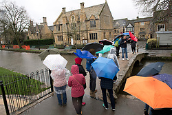 © Licensed to London News Pictures. 08/02/2019. Bourton-on-the-Water, Gloucestershire, UK. Tourists cross a bridge  holding umbrellas during a rain shower on a wet and windy day in Bourton-on-the-Water in Gloucestershire, UK. Photo credit: LNP