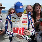 NASCAR Sprint Cup driver Dale Earnhardt Jr. (88)  sign autographs in the garage area during the NASCAR Coke Zero 400 Sprint practice session at the Daytona International Speedway on Thursday, July 4, 2013 in Daytona Beach, Florida.  (AP Photo/Alex Menendez)