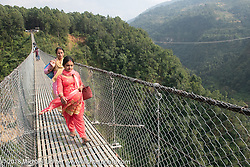 Nepali's crossing the Kusma Gyadi Bridge, the tallest (443') and one of the longest (1,128') suspension bridges in the country that cut a hike of many hours to just a few minutes. Day-7 of our Himalayan Heroes adventure riding from Tatopani to Pokhara, Nepal. Monday, November 12, 2018. Photography ©2018 Michael Lichter.
