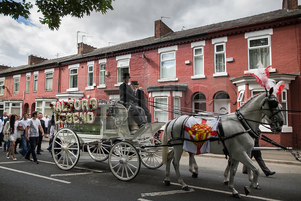 """© Licensed to London News Pictures . 28/08/2015 . Salford , UK . The procession passes along Liverpool Street , watched by people lining the pavements . The funeral of Paul Massey at St Paul's CE Church in Salford . Massey , known as Salford's """" Mr Big """" , was shot dead at his home in Salford last month . Photo credit : Joel Goodman/LNP"""