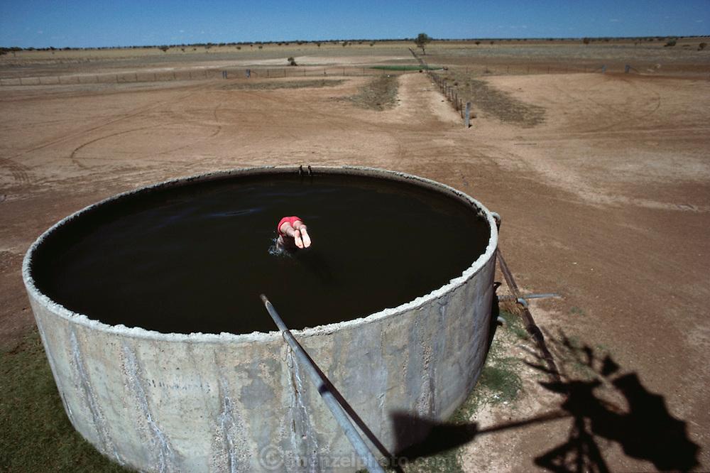 Peter Menzel cools off in a water tank south of Walgett, NSW, Australia.  MODEL RELEASED.