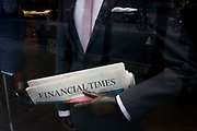 The Financial Times in the arm of a central London menswear shop mannequin. With the folded newspaper in the crook of its arm, the model has polished wooden hands and a well-fitted suit and shirt showing both class and luxury with a hint of knowledge and education. The Financial Times (FT) is an English-language international daily newspaper with a special emphasis on business and economic news. The paper, published by Pearson in London, was founded in 1888 by James Sheridan and Horatio Bottomley, and merged with its closest rival, the Financial News (which had been founded in 1884) in 1945.