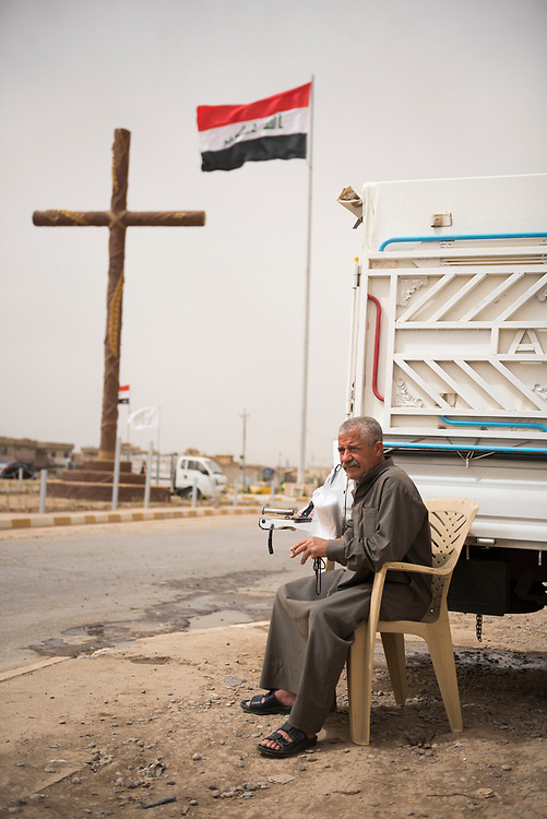 At the entrance to Qaraqosh, Bashar Azoo Boutros Alkhashanna, a 50-year-old Syriac Catholic, sells ice from the back of a truck. Qaraqosh, located a few kilometers from Mosul, was Iraq's largest Christian town until 2014, when residents fled the ISIS advance. (May 20, 2017)